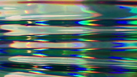 Abstract and attractive Closeup footage of grunge holographic foil. Multicolor surface and shiny background with waves.