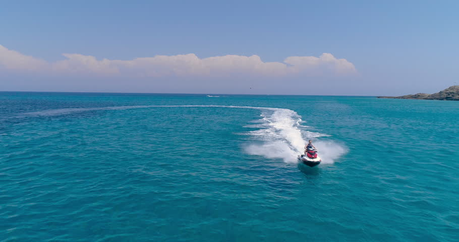 Aerial View Over Man Speeding On Jet Ski Tourist Attraction Exotic Tropical Island Shore Beach At Exotic Greek Island Extreme Sports Vacation Trip Tourism Sport Attraction Paradise Adventure Concept