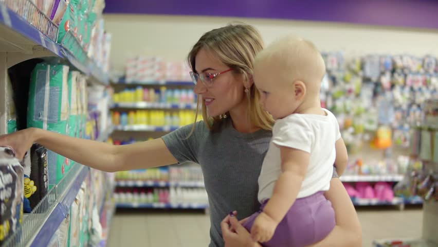 Young attractive mother in glasses holding her child in her arms while choosing diapers on the shelves in the supermarket. Thoughtful mom carefully choosing best products for her child #30139450