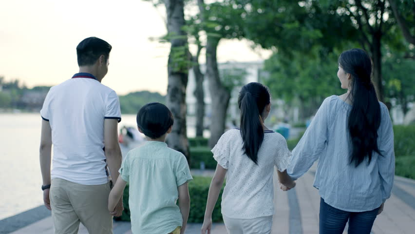 Rear view of asian family of 4 walking on waterfront promenade at dusk