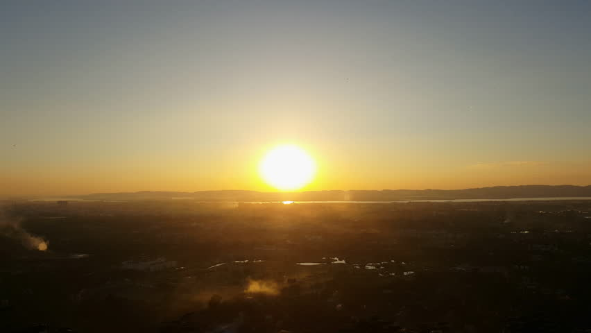 Sunset on horizon, Mandalay cityscape high angle shot, smoke, birds fly, sky