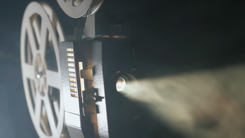 Front view of an old-fashioned antique Super 8mm film projector, projecting a beam of light in a dark room next to a stack of unraveled film reels. Royalty-Free Stock Footage #30171919