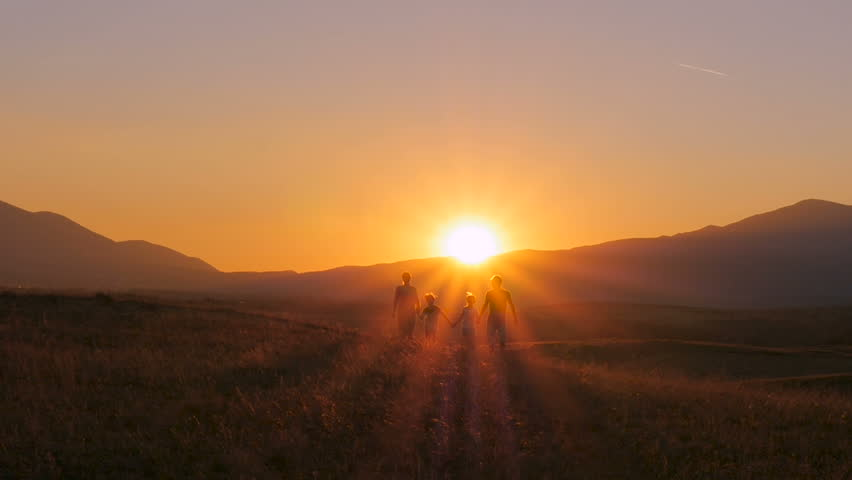 A happy family runs to meet the sun holding hands on the mountainside. Backlight. Beautiful sunset. | Shutterstock HD Video #30187339