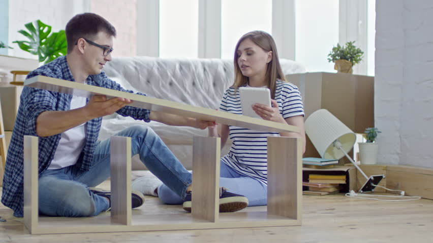 PAN of happy young man in glasses sitting on floor of new apartment and assembling wooden shelf while beautiful woman with tablet giving instructions #30202342