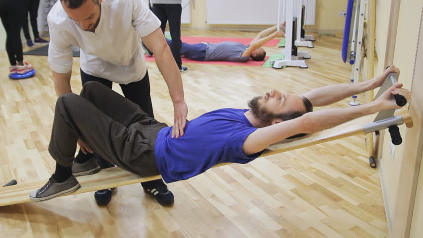 Physiotherapist helping young man, doing exercises at the rehabilitation center. Healthy gymnastics. Active people.