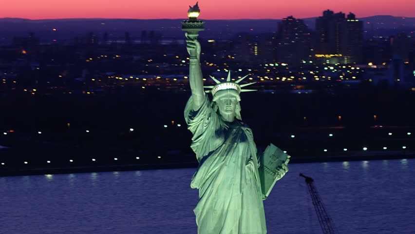 Aerial view of the Statue of Liberty at dusk. Manhattan and New Jersey skyline. New York City, United States. Close-up. Shot from helicopter.