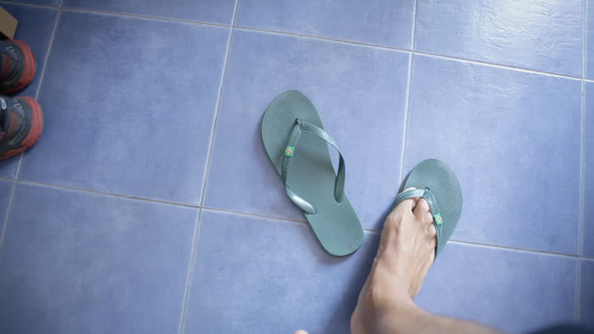POV of the feet of a man at home, putting his summer flip flops on and entering a dark room.