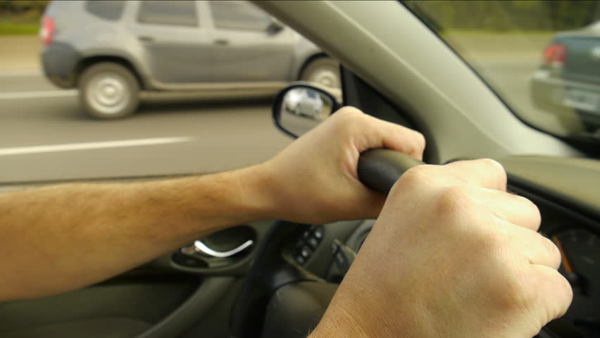 Driving a car on the freeway. Male hands and on steering wheel. close Up.