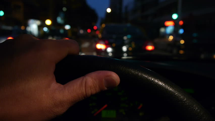 Driving at night on the city. -Hand on steering wheel close up. POV.