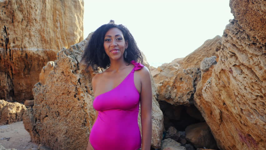 Portrait of black people, pretty happy young african american woman looking at camera and smiling.Rocks beach.Sexy mixed race girl in pink swimsuit and jewelry enjoying nature.Slow motion.