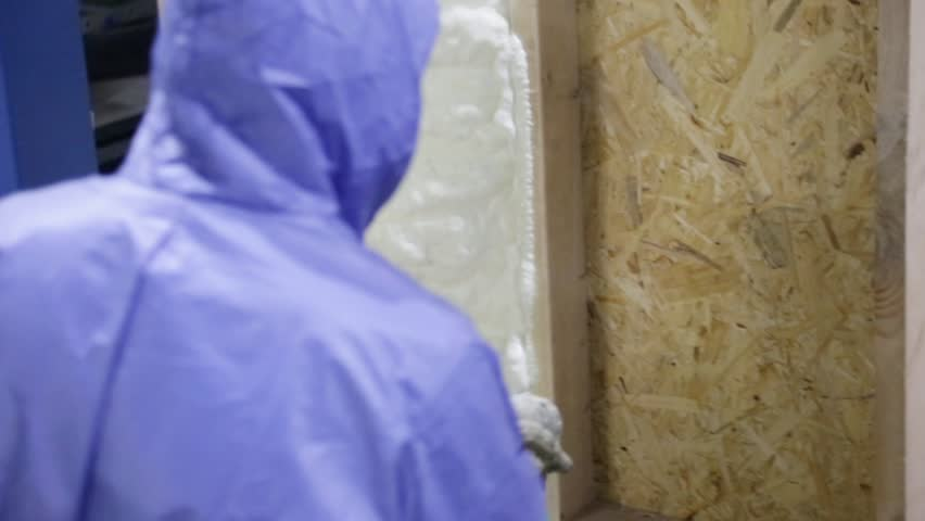 The builder applies foam from a special gun on a wooden wall