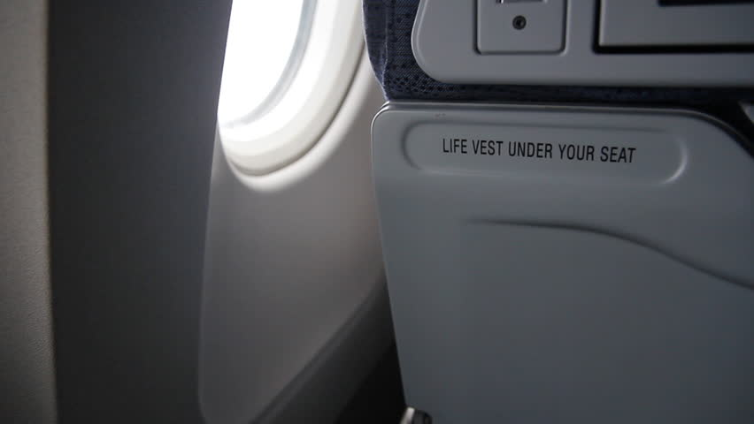 Detail of plane seat with 'Life vest under your seat' notice. Two shots taken inflight on a commercial jet.