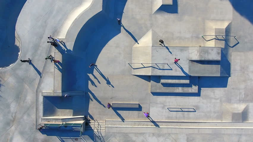 Aerial 4K Drone footage of Sidewalk Surfers. The moving drone captures the action, the shadows and the skills of skateboarders performing stunts over cement geometric shapes.