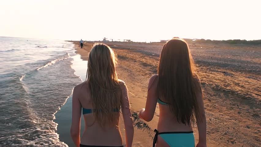 Girls running around on the beach.