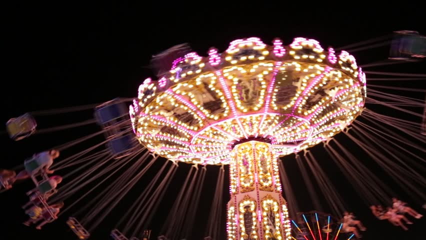 Popular Chair Swing Rides in Amusement Park. Carousel with lights. Night shooting. Looped. Festive fun at the fair