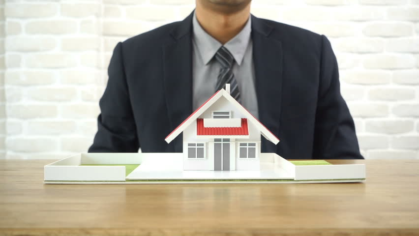 Businessman covering and protecting home with his hands - property and real estate insurance concept