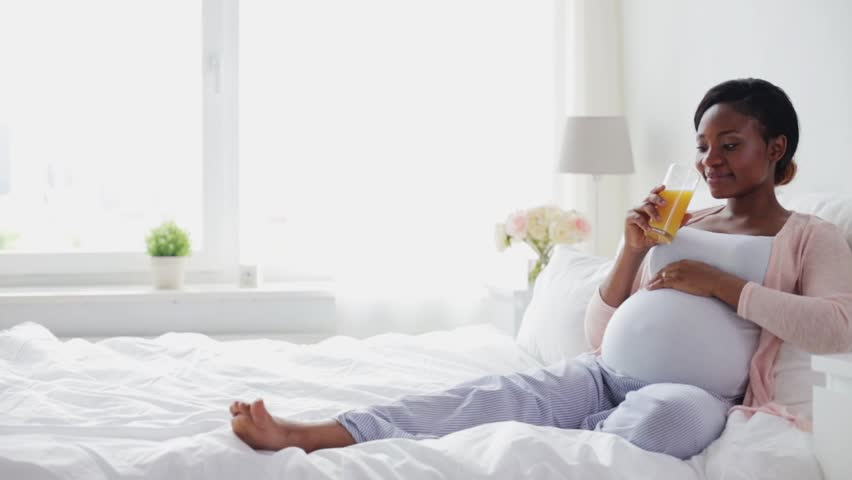 Pregnancy, healthy eating, diet and people concept - happy pregnant african american woman drinking fresh orange juice in bed