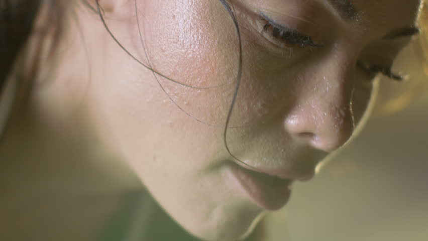 Close-up Shot of a Beautiful Athletic Woman Wipes Sweat from Her Forehead with a Hand, Looks into Camera. She's Tired after Intensive Cross Fitness Exercise. Shot on RED EPIC-W 8K Helium Cinema Camera