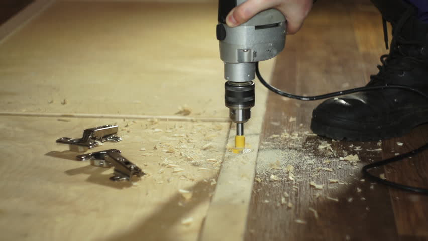 Close-up forstner bit drills wood. The joiner with manual electric drill cut a hole in the wooden door to install the hinges, slow motion. #30317353