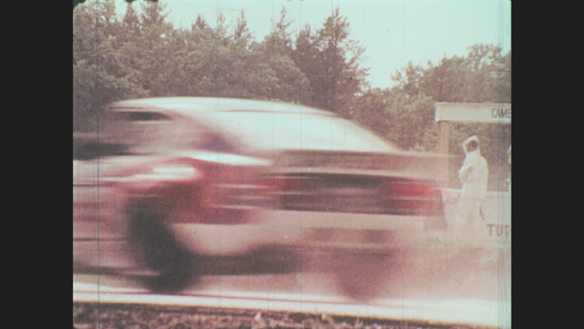 1970s: People in rain gear wave flag. Cars speed by flaggers. Race car drives on track. Race cars drive on track. Race car spins out on curve. Race car slides off track. Cars drive down rainy highway.