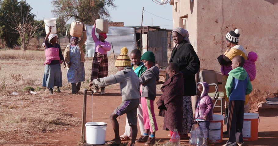 Poor people in Africa unable to maintain social distance to prevent Covid 19, due to overcrowding and poverty Young african boys drinking water from a tap while woman line up to collect water in cont Royalty-Free Stock Footage #30325846