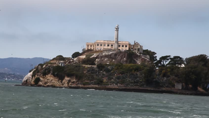 Sea view leaving the Alcatraz island prison by boat. Bay of San Francisco, United States. Warden's house and lighthouse. Concept of escape and freedom. Popular tourist attraction in San Francisco.