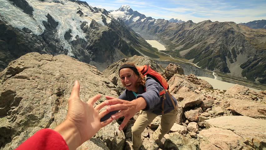 Young woman hiking pulls out his hand to get assistance from teammate.