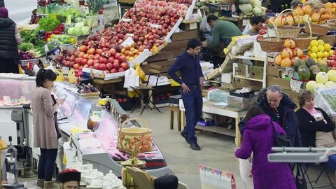 MOSCOW - JAN 18, 2017: Sellers work near stalls with fruits and vegetables in Danilovsky food market