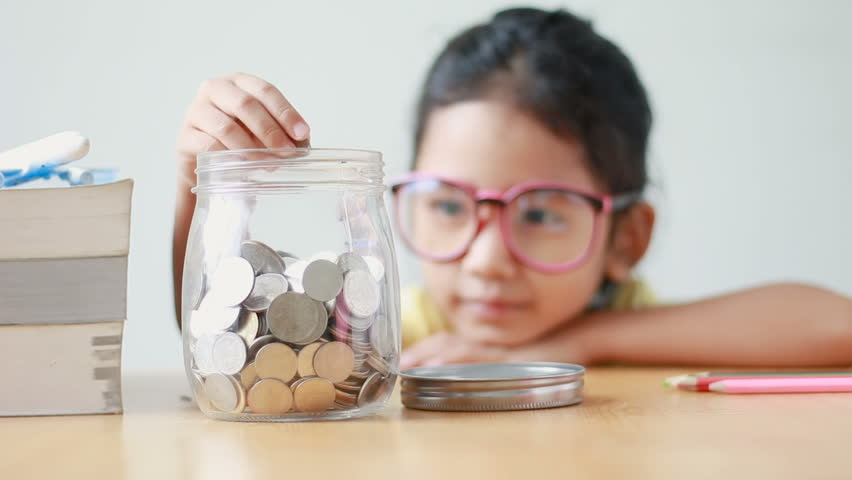 Asian little girl putting the coin into a  clear glass jar on table metaphor saving money concept with sound select focus on jar #30352252