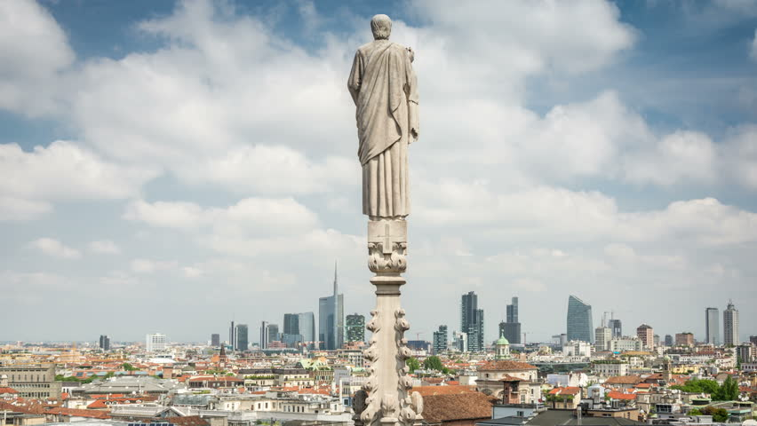 Panoramic view of Milan from the rooftop of the Duomo di Milano. City skyline. White clouds move fast across the blue sky. Time lapse video.   Shutterstock HD Video #30365665