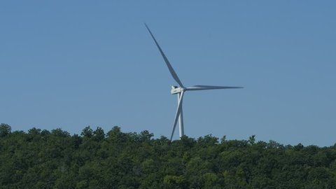 Closer up shot of a wind turbine rotating in the distance