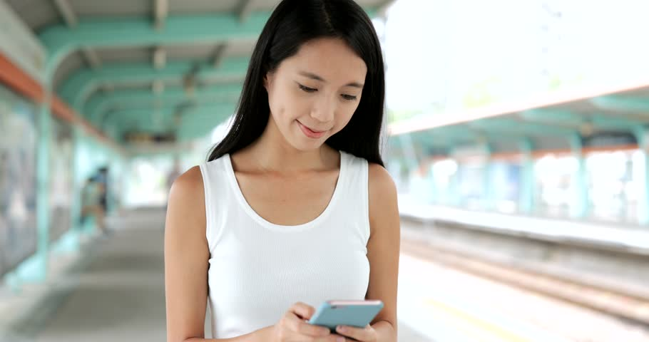 Woman walking in the light rail platform and using cellphone  #30375319