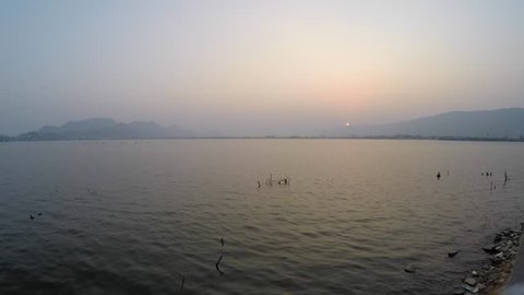 A time lapse of a sunset view with a clear view of the river in the foreground, and mountains in the background, in North India.