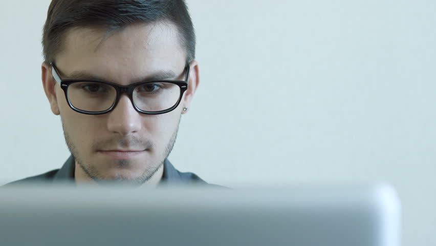 Close-up portrait of a young man wearing glasses sitting in his office in front of a monitor - working on a computer. People stock footage slider shot. | Shutterstock HD Video #30378568