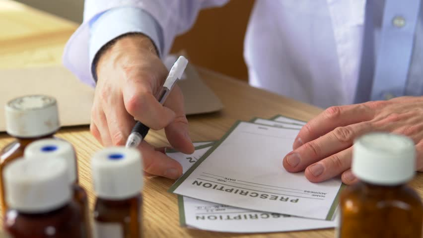 Doctor writing a prescription on his desk with drug tablets to the side. Healthcare and pharmacy. No faces shown, In 4K. | Shutterstock HD Video #30396634