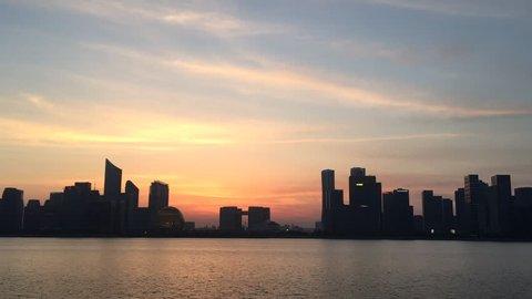 modern buildings in hangzhou qianjiang new city at sunset from bank