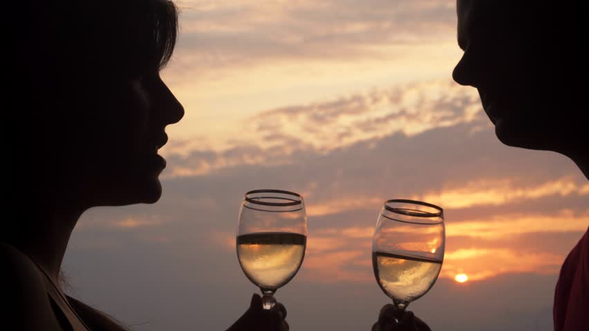 Couple is toasting with wine glasses during a beautiful summertime sunset. | Shutterstock HD Video #30406087