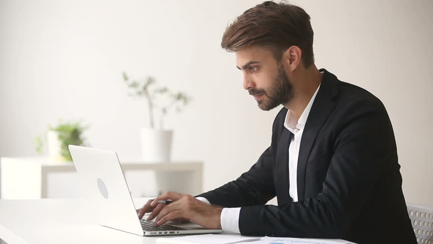 Young businessman wearing suit sitting at office desk using  laptop, answering call on the phone, consulting client about e-mail by cell, booking ordering services by cellphone | Shutterstock HD Video #30408655