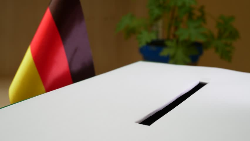 After Vote, the Hand Drops the Ballot into The Special Box With National Flag Of Germany On Elections. Ballot Box in Germany