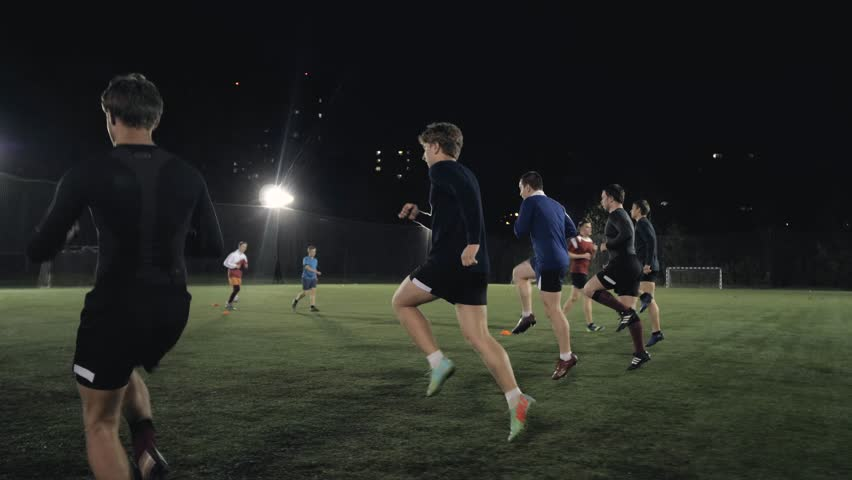 Soccer football players during the team training before the match. Exercises for football soccer youth team. Young player exercises with ball and marker cones, running training rugby men athlete