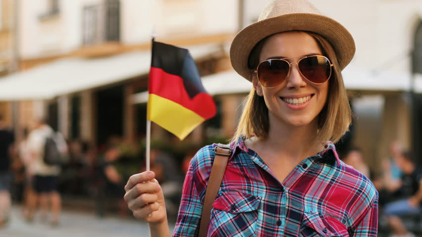 Happy attractive woman with germany flag posing on camera and smiling on the city street background. close up