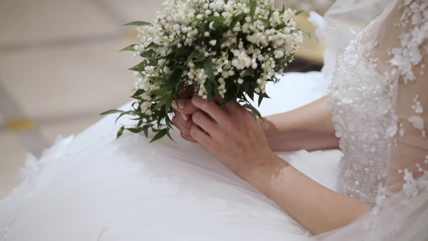 Bride sitting with bouquet indoors #30428395