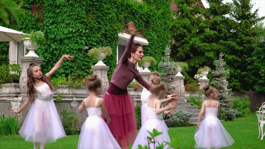 Teachers together with smoy schoolgirls dance the ballet in a garden of ballet school. Ballerinas dance on a lawn in a garden. | Shutterstock HD Video #30437350