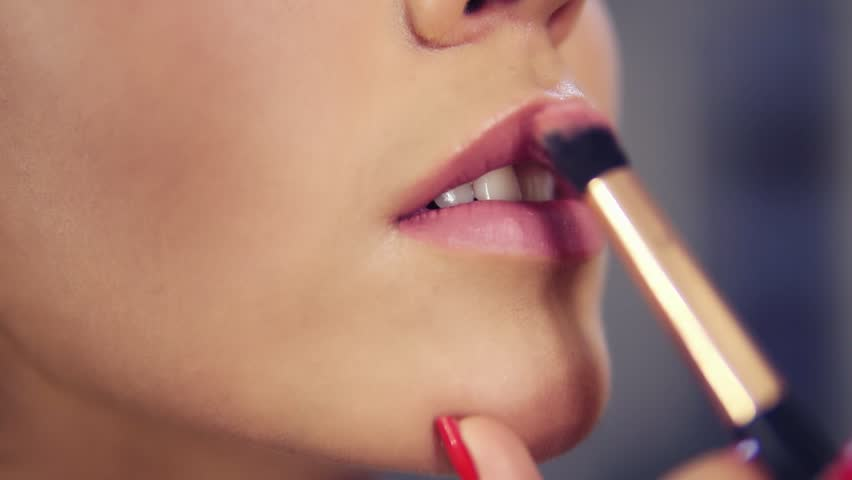 Closeup view of a professional makeup artist applying lipstick on model's lips working in beauty fashion industry. Closeup view of an artist's hand using special brush
