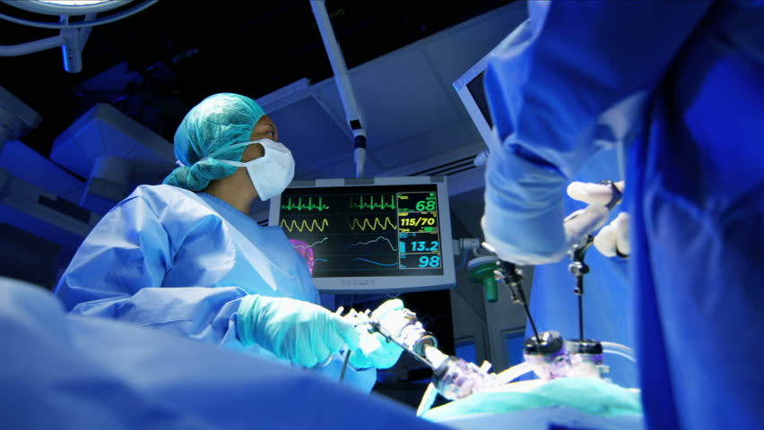 Reveal Medical surgical training hospital performing Laparoscopic operation by Caucasian male and female specialist team in scrubs and African American Anesthesiologist RED WEAPON