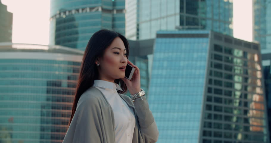 Steadicam shot of a young beautiful Asian girl in a great mood on the way to work, with skyscrapers in the background talking on the phone