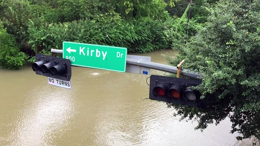 A street sign hanging over a flooded street after Hurricane Harvey came through town.