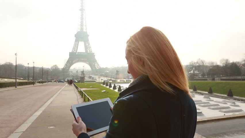 Tourist at the Eiffel tower using digital tablet to take a picture  Young woman taking pictures of the Eiffel Tower in Paris, France  | Shutterstock HD Video #30470542