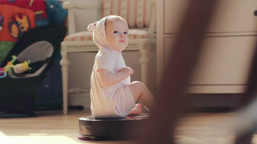 Little girl baby with pleasure riding on a robot vacuum cleaner in children room