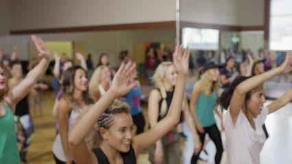 Medium panning shot of people dancing in exercise class / Orem, Utah, United States